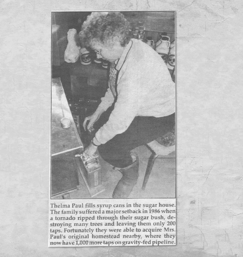 """Newspaper print of Thelma Paul. Caption reads: """"Thelma Paul fills syrup cans in the sugar house. The family suffered a major setback in 1986 when a tornado ripped through their sugar bush, destroying many trees and leaving them only 200 taps. Fortunately, they were able to acquire Mrs. Paul's original homestead nearby, where they now have 1,000 more taps on gravity-fed pipeline."""""""