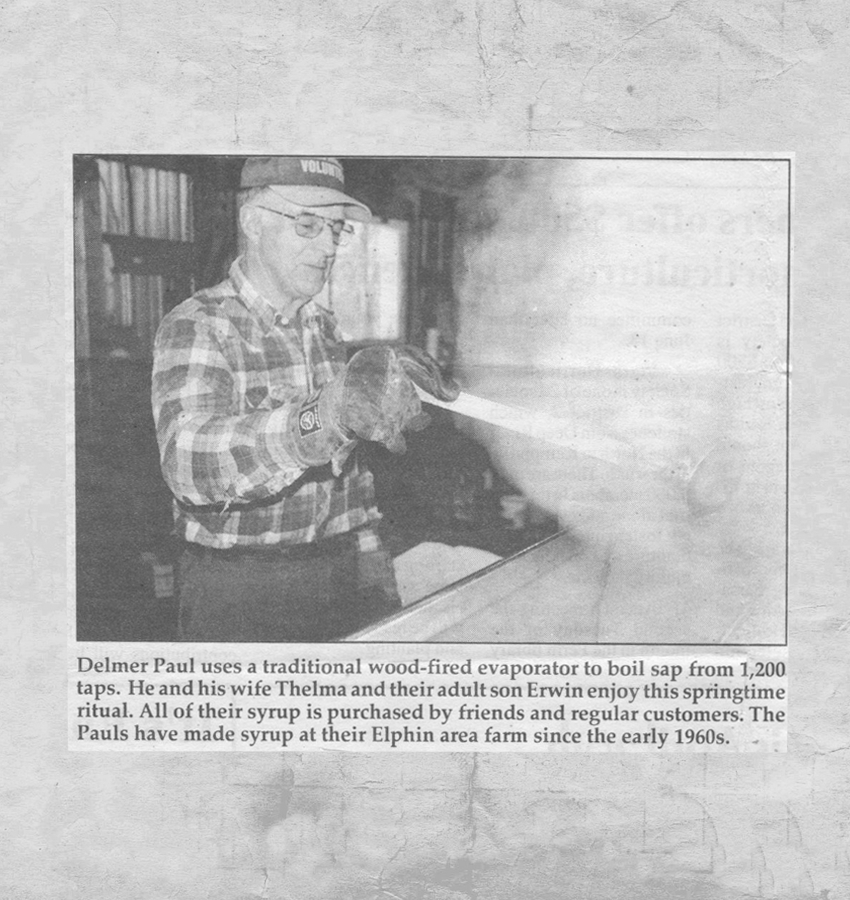 """Newspaper print of Delmer Paul. Caption reads: """"Delmer Paul uses a traditional wood-fired evaporator to boil sap from 1,200 taps. He and his wife Thelma and their adult son Erwin enjoy this springtime ritual. All of their syrup is purchased by friends and regular customers. The Pauls have made syrup at their Elphin area farm since the early 1960s."""""""