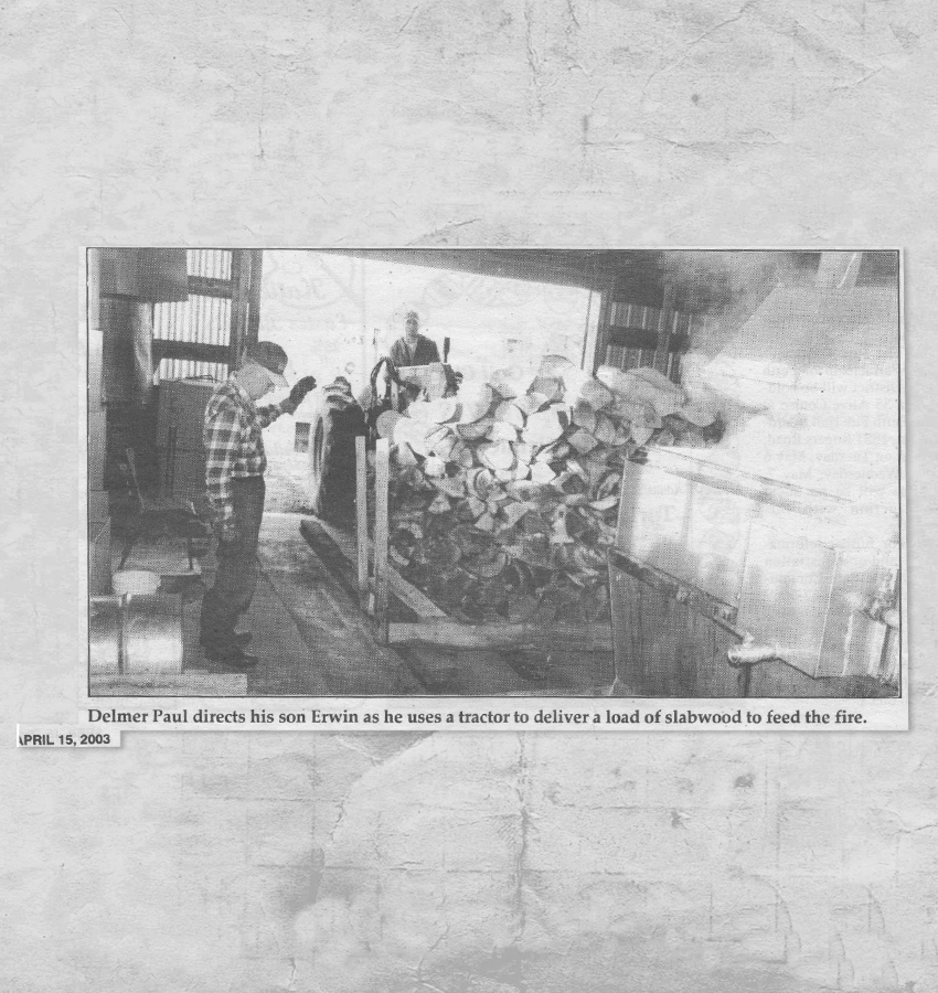 """Newspaper print. Caption reads: """"Delmer Paul directs his son Erwin as he uses a tractor to deliver a load of slabwood to feed the fire. April 15, 2003"""""""