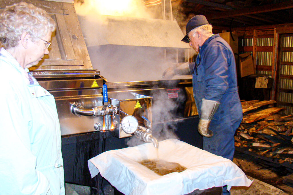Thelma and Delmer making maple syrup